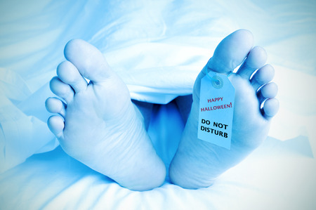 closeup of the feet of a dead body covered with a sheet and with a tag tied on his big toe with the text happy halloween, do not disturb Stock Photo
