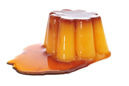 caramel sauce: a creme caramel topped with caramel sauce on a white background
