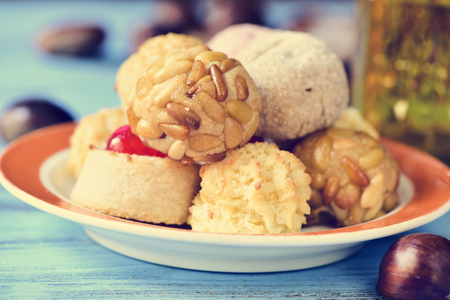 panellets: a plate with some different panellets, typical pastries of Catalonia, Spain, eaten in All Saints Day, and some chestnuts on a blue rustic wooden table Stock Photo