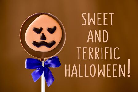 terrific: a pumpkin-shaped chocolate lollipop and the text sweet and terrific halloween against a brown background