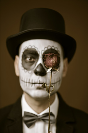 skeleton costume: portrait of a young man with calaveras makeup, wearing bow tie and top hat, with a dry rose in front of his eye, with a vintage effect