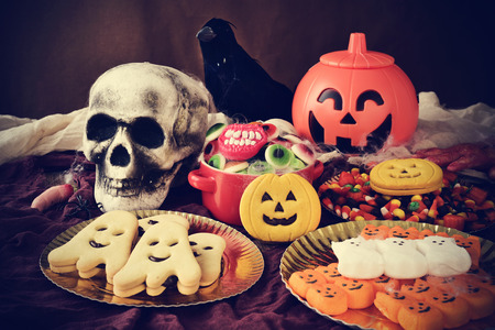 scary pumpkin: different Halloween candies and cookies on a table decorated with some scary ornaments, such as a skull, a black crow or a carved pumpkin