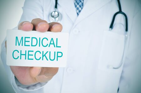 geriatrician: closeup of a young doctor man showing a signboard with the text medical checkup written in it Stock Photo