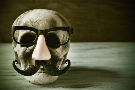 squelette: a scary and funny skull with eyeglasses, fake nose and mustache on a rustic wooden surface, with a filter effect Banque d'images