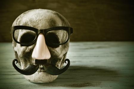 esqueleto: un cráneo de miedo y divertido con gafas, nariz falsa y bigote en una superficie de madera rústica, con un efecto de filtro