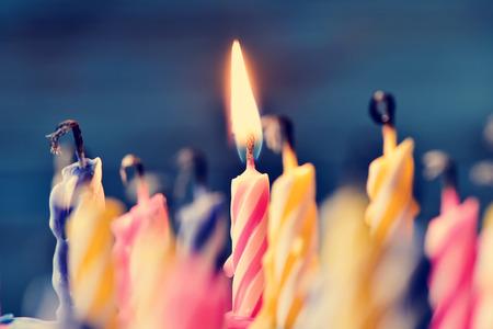 gros plan de quelques bougies éteintes et juste une bougie allumée après avoir fait sauter le gâteau