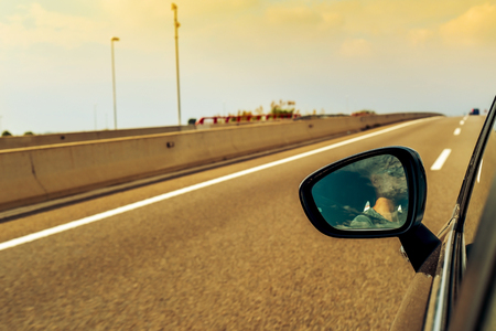 travelling salesman: a young man, reflected in the wing mirror, driving a car in a road with several lanes Stock Photo