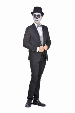 skull character: full length portrait of an elegant man with calaveras makeup, wearing jacket, bow tie and top hat, on a white background