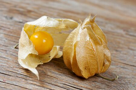 inca: closeup of some groundcherries with husk on a rustic wooden surface Stock Photo