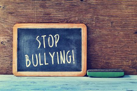 de tekst stop pesten geschreven met krijt op een schoolbord en een gum op een blauwe rustieke houten bureau in een klaslokaal