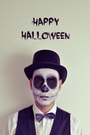 skelett mensch: Portr�t eines Mannes mit calaveras Make-up ohne Augen, tr�gt Fliege und Hut, und den Text gl�ckliches Halloween
