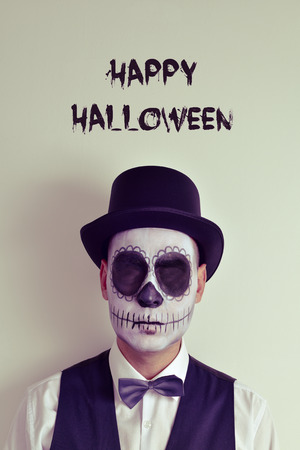 skeleton costume: portrait of a man with calaveras makeup without eyes, wearing bow tie and top hat, and the text happy halloween