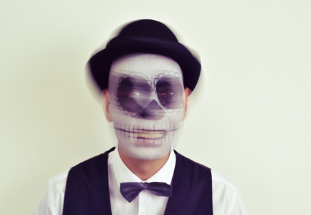 funny face: portrait of a man with calaveras makeup, wearing bow tie and bowler hat, in motion