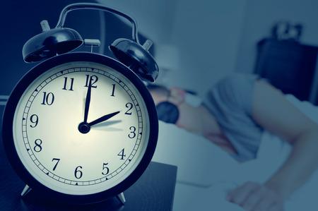 Gros plan d'un réveil sur une table de chevet réglage reculera d'une heure à la fin de l'heure d'été, tandis qu'un jeune homme dort dans son lit Banque d'images