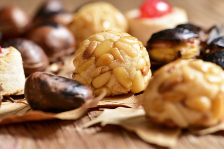 panellets: closeup of some roasted chestnuts and some panellets, typical snack in All Saints Day in Catalonia, Spain, and dry leaves on a rustic wooden surface