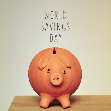 profit celebration: an earthenware piggy bank on a wooden table and the text world savings day Stock Photo