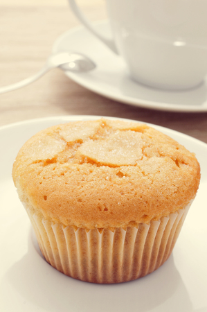 madalena: closeup of a magdalena, a typical spanish plain muffin, in a white plate on a set table with a cup of coffee in the background