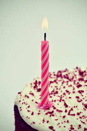 lighted: closeup of a cake with a lighted candle, with a slight vignette added