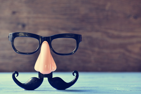 een valse snor, neus en bril op een rustieke blauwe houten oppervlak