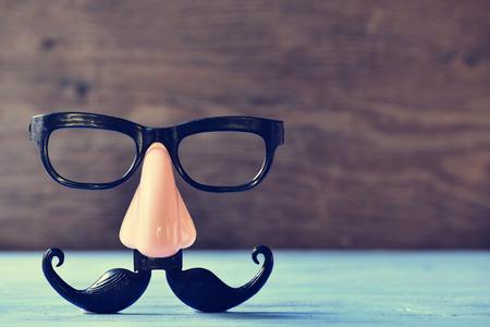 nariz: un bigote falso, la nariz y las gafas sobre una superficie de madera azul rústico