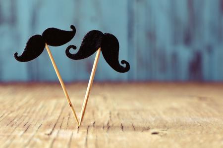 sexo: dos bigotes de fieltro en diferentes palos en una superficie de madera rústica