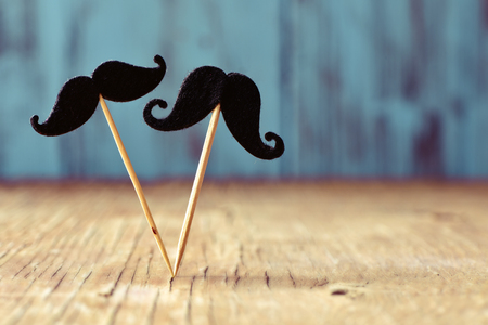 sex symbol: two different felt mustaches in sticks on a rustic wooden surface