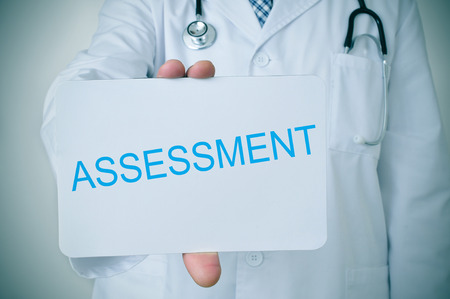 geriatrician: closeup of a young doctor man showing a signboard with the word assessment written in it
