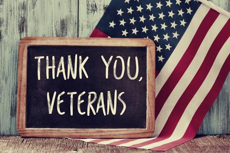 felicitaciones: el texto gracias veteranos escritos en una pizarra y una bandera de los Estados Unidos, en un fondo de madera rústica