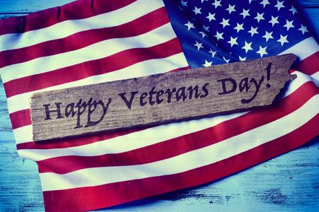 day: el día de veteranos feliz de texto escrito en un pedazo de madera y una bandera de los Estados Unidos, sobre un fondo azul de madera rústica