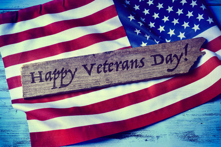 remembrance day: the text happy veterans day written in a piece of wood and a flag of the United States, on a blue rustic wooden background Stock Photo