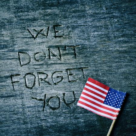 古い木製表面とアメリカ合衆国の旗に刻まれた私たちを忘れないでくださいテキスト