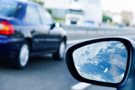 travelling salesman: a young man, reflected in the wing mirror, driving a car in a road with several lanes, being passed by another car Stock Photo