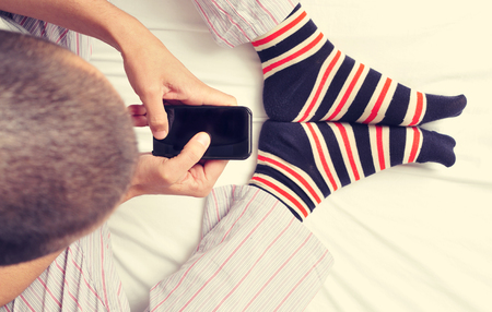 striped pajamas: high-angle shot of a young caucasian man wearing pajamas and colorful striped socks using a smartphone in bed