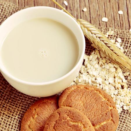 avena en hojuelas: primer plano de una taza con leche de avena, una espiga de trigo, algunos copos de avena y galletas digestivas en una mesa de madera r�stica Foto de archivo