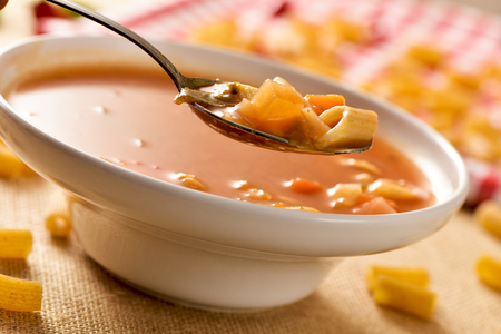 minestrone: closeup of a bowl with minestrone, a typical italian soup, with vegetables and pasta, on a set table Stock Photo