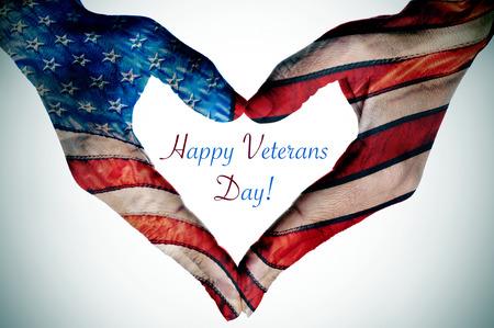 de tekst happy veteranen dag en de handen van een jonge vrouw die een hart patroon met de vlag van de Verenigde Staten