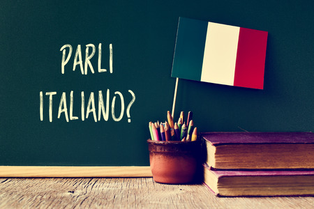 bandiera italiana: una lavagna con la domanda Parli italiano? parli italiano? scritto in italiano, una pentola con matite, alcuni libri e la bandiera d'Italia, su una scrivania in legno Archivio Fotografico