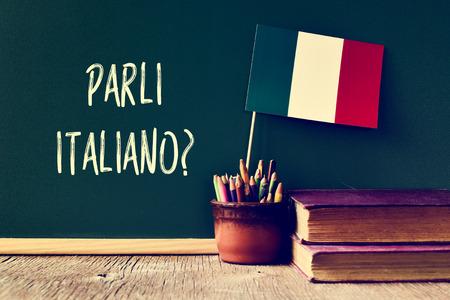 idiomas: una pizarra con la cuestión Parli italiano? ¿hablas italiano? escrito en italiano, un bote con lápices, algunos libros y la bandera de Italia, en un escritorio de madera
