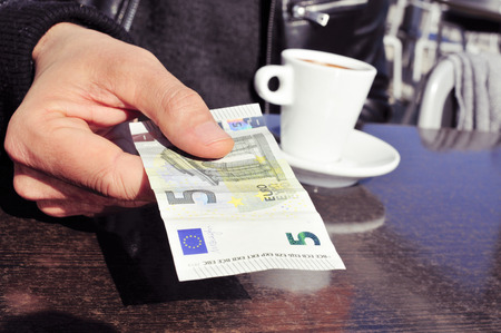 decaffeinated: closeup of a young man with a cup of coffee paying the bill in the terrace of a cafe with a five euros banknote