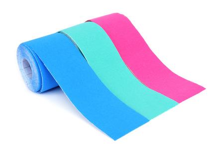 さまざまな色、ピンクや青、白い背景の上の 2 つの異なる色合いのキネシオ テープのいくつかのロール 写真素材