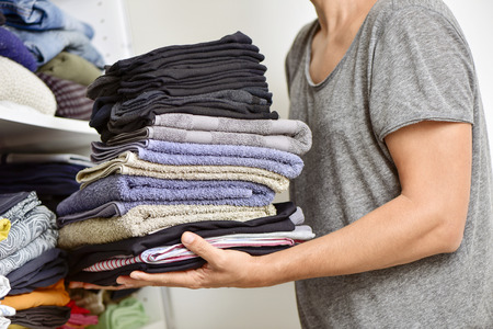 pile of clothes: closeup of a young man carrying a pile of different folded clothes