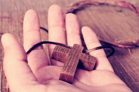 spiritualism: a wooden cross in the hand of a young man and a depiction of the crown of thorns of the Christ on a rustic wooden surface, with a filter effect
