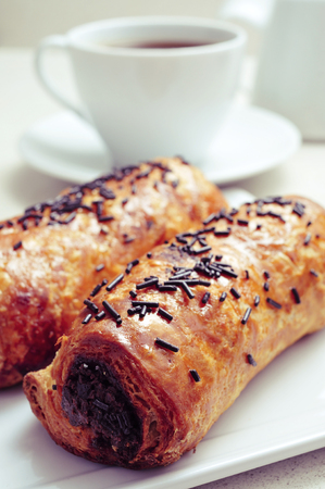 chocolat: closeup of some pain au chocolat and a cup of coffee on a set table for breakfast