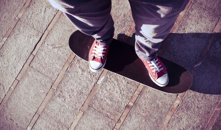 skate board: self-portrait of a young man wearing red sneakers on a skate board