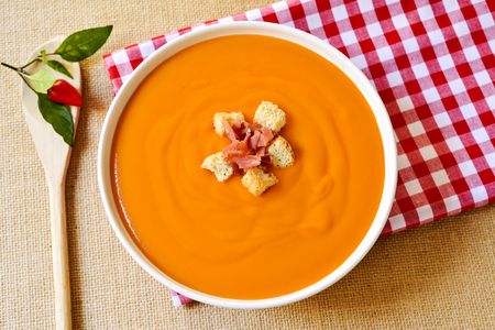 andalusian cuisine: high-angle shot of a bowl with spanish salmorejo cordobes or porra antequerana, with serrano ham and croutons, on a set table