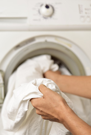 closeup of a young man introducing or taking out a white sheet into a washing machine or a clothes dryer Archivio Fotografico