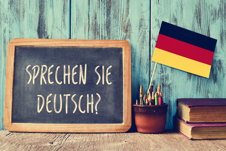 Eine Tafel mit der Frage Do you speak English? Sprichst du deutsch? auf Deutsch geschrieben, ein Topf mit Bleistiften, einige Bücher und der Flagge von Deutschland, auf einem hölzernen Schreibtisch