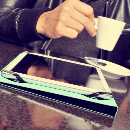 decaffeinated: closeup of a young man taking a cup of coffee with a tablet computer on the table, in the terrace of a cafe