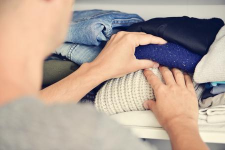 ropa de invierno: primer plano de un hombre caucásico joven organizar el armario
