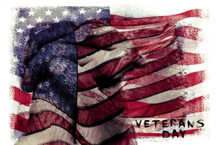 dia: el Día de los Veteranos de texto escrito en una doble exposición de una bandera de los Estados Unidos y un primer plano de las manos entrelazadas de un hombre de oración Foto de archivo